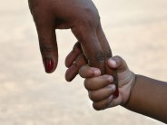 black mothers hand holding childs hand